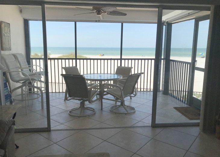 Condo opens to lanai with 2 screens & steps down to patio/beach.