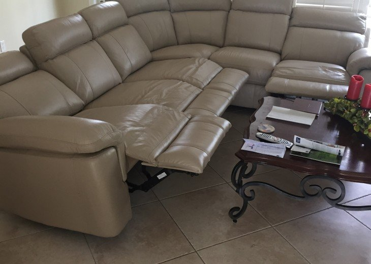 New leather reclining sofa in open floor plan to kitchen off pool