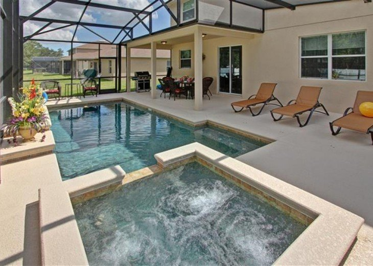 Screened backyard with heated pool and spa, BBQ, dinning table and lounge chairs