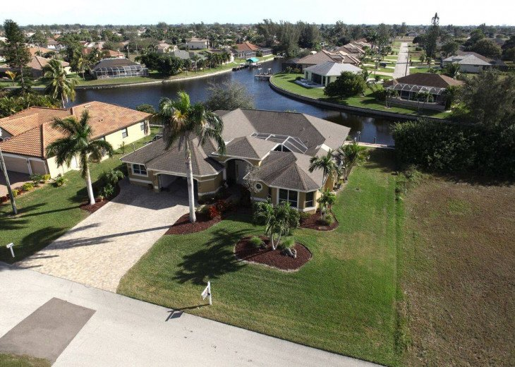 Arial view of house on large lot with intersection canal back yard